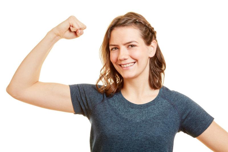 Starke junge Frau spannt ihren Bizeps Muskel im Arm an