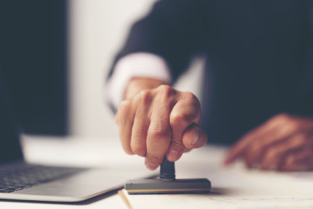 Hand stempelt ein Dokument mit Laptop im Hintergrund