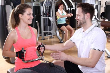 Fitnesstrainer weist Frau am Ruderzug ein