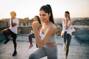 Group Fitness Trainerin leitet Gruppe auf einem Dach