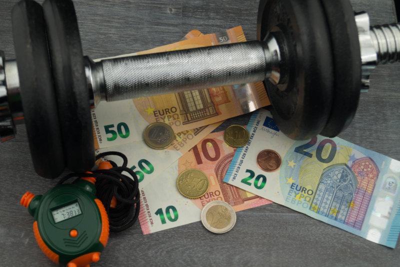 Geldscheine, Stoppuhr und Hantel