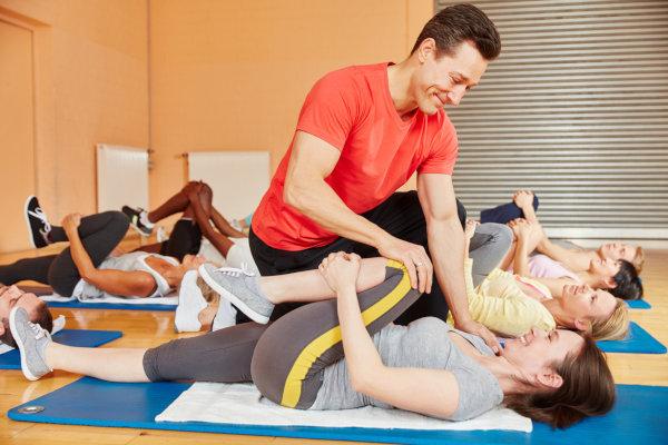 Fitnesstrainer hilft bei Dehnungsübung im Gymnastik Kurs