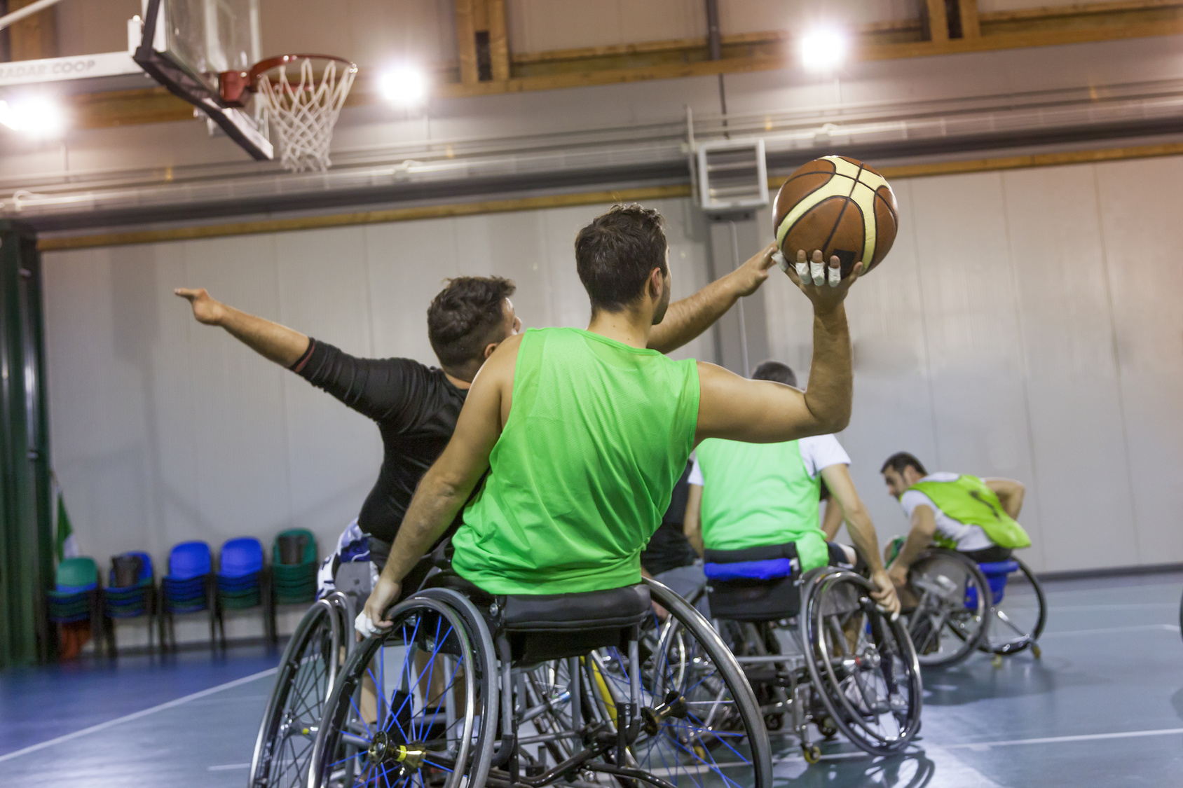Zwei Mannnschaften spielen Rollstuhl Basketball gegeneinander