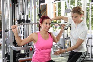 Fitnesstrainer weist Frau beim Latzug