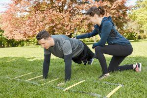 Frau trainiert Mann als selbstständige Fitnesstrainerin im Park