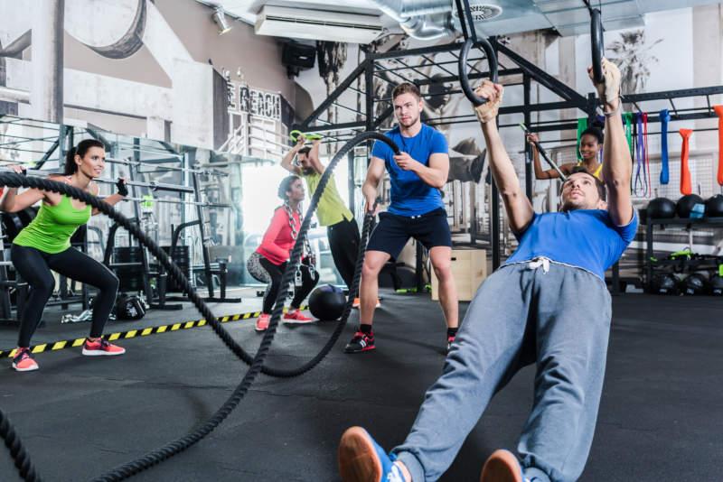 Vier Personen trainieren mit unterschiedlichen Geräten im Fitnessstudio