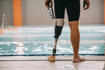 Schwimmer mit Beinprothese steht am Beckenrand