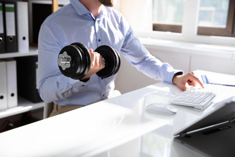 Mann im Hemd sitzt am Schreibtisch und trainiert mit einer Hantel