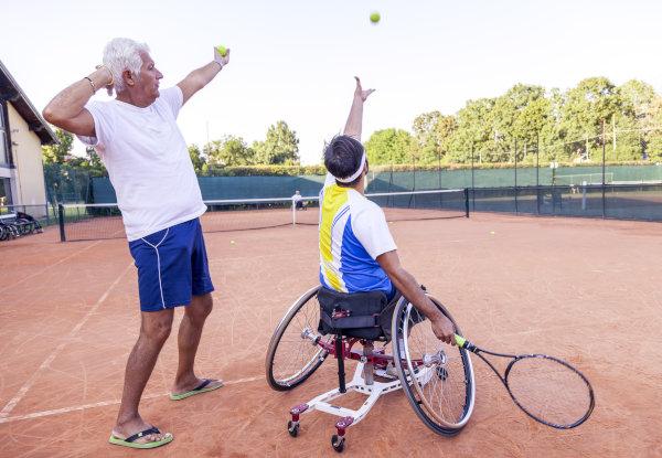 Trainer bring Athlet im Rollstuhl den Tennisaufschlag bei
