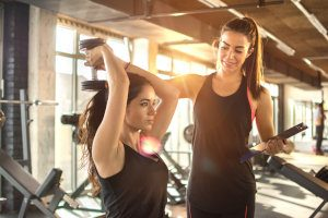 Personal Trainer trainiert Frau bei Übung mit Gewichten