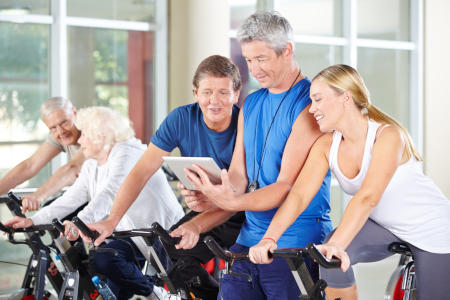 Trainer mit Tablet PC trainiert eine Gruppe Senioren im Fitnesscenter