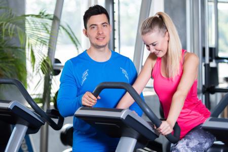 Fitnesstrainer und Frau beim Training